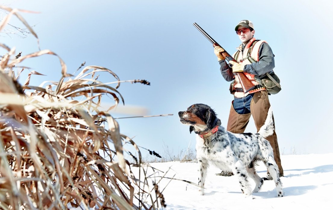 Hunter in outdoor equipment holding a gun with a dog