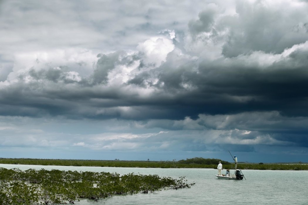 Men fishing on a boat near the ocean with stormy clouds