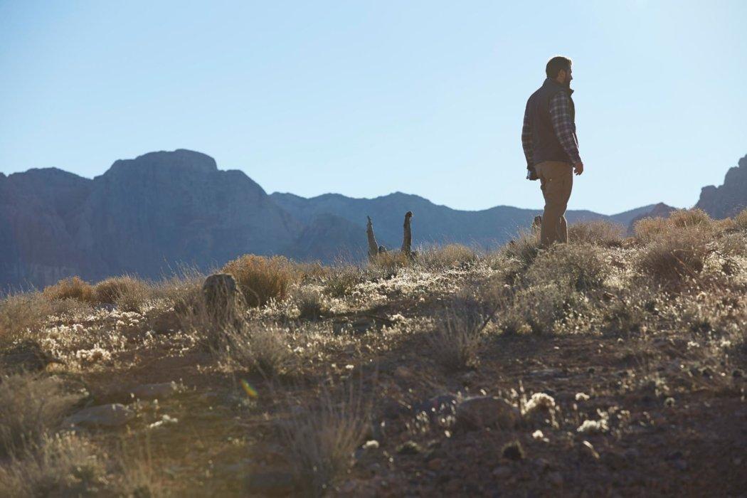 Man standing on ridge in an arid land - lifestyle photography