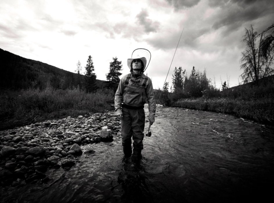Fly fisherman black and white in a stream