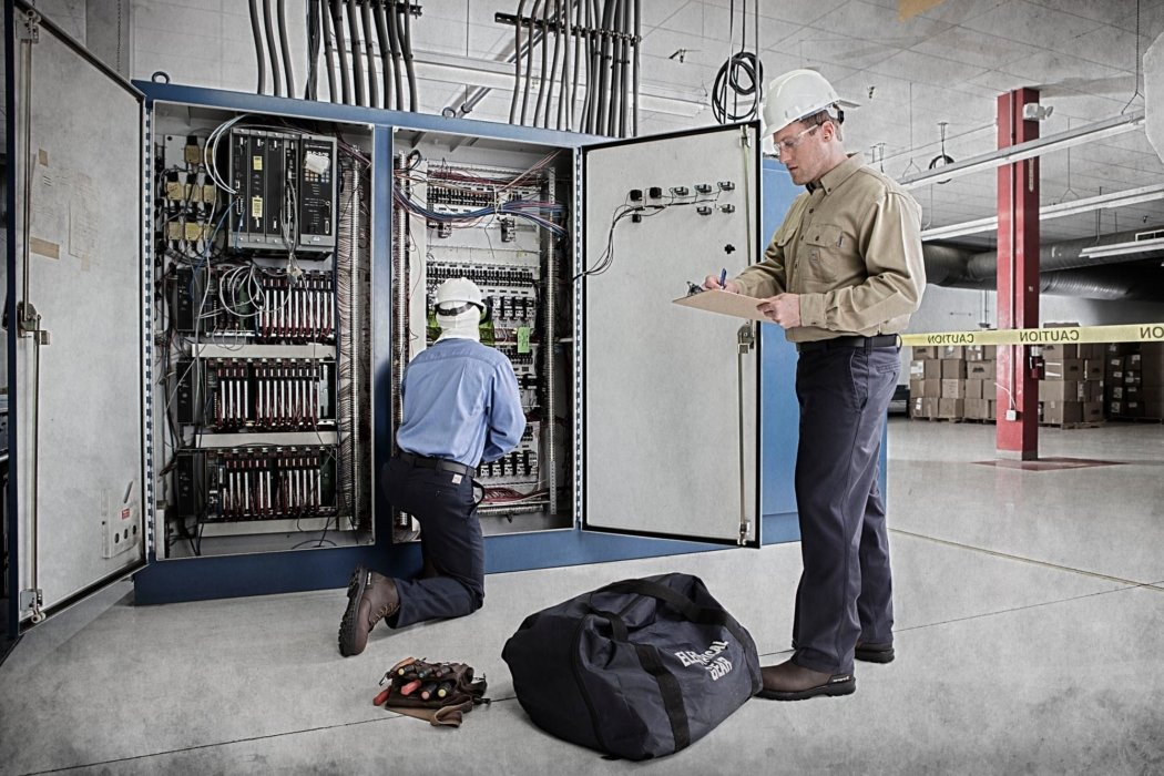 Two workers working on an electrical box