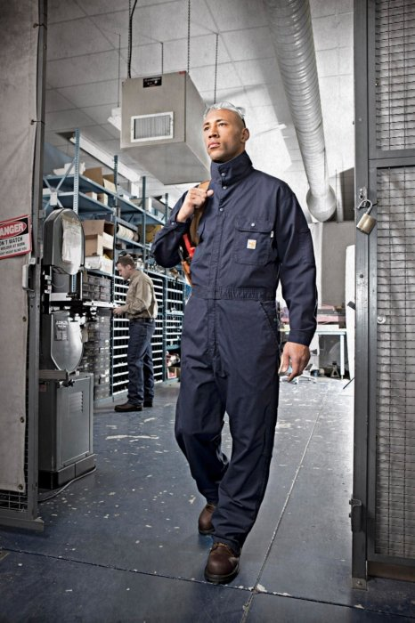 A worker in a jumpsuit walking through a facility
