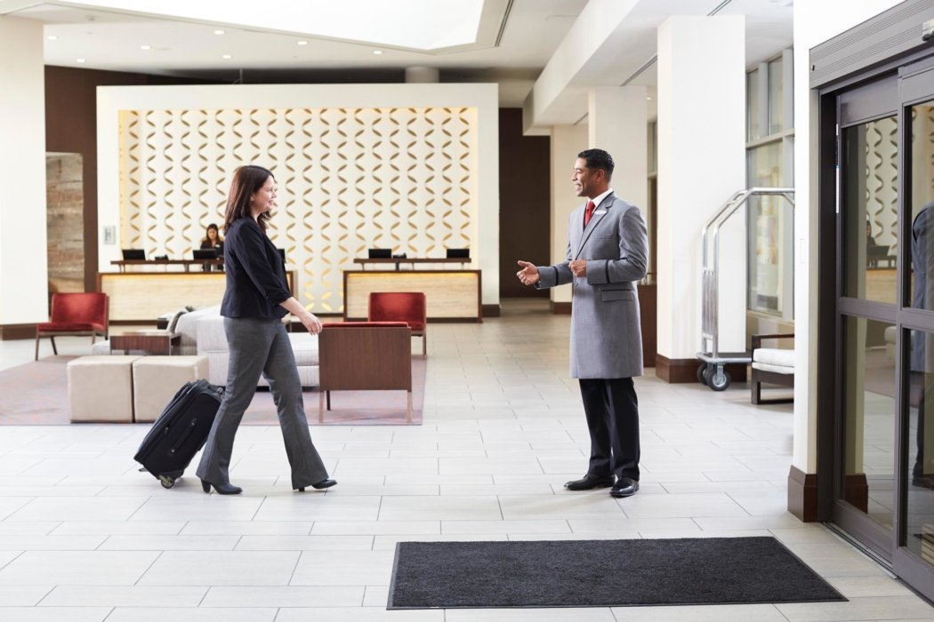 A worker and customer in a hotel lobby