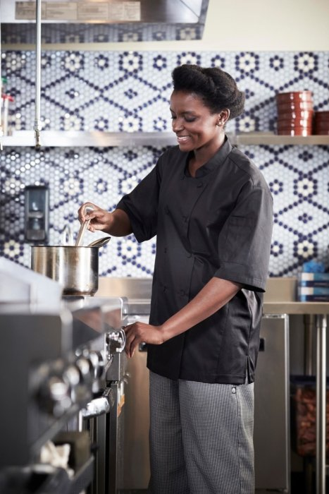 A chef stirring soup in a kitchen