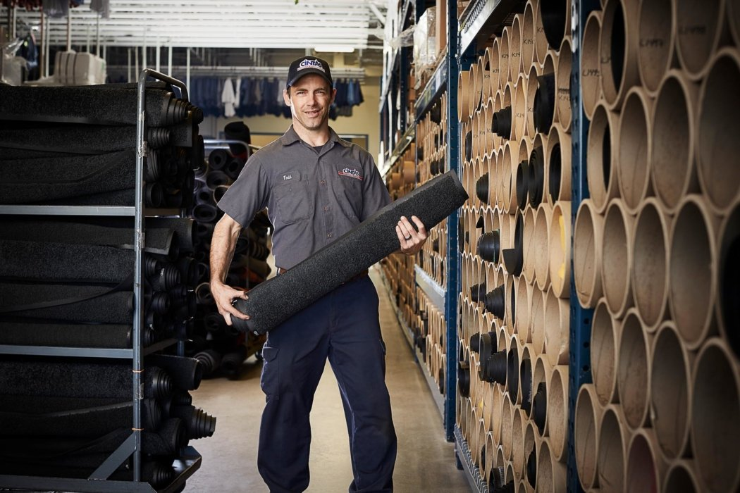 A worker portrait holding a roll of textiles
