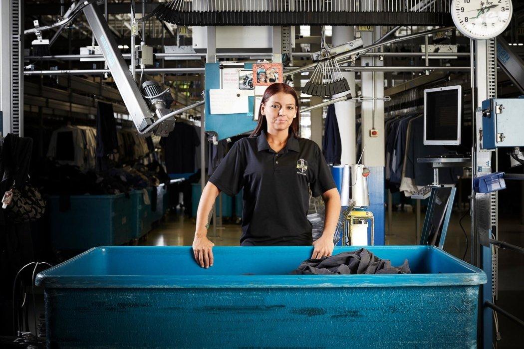 A woman worker standing next to a blue bin