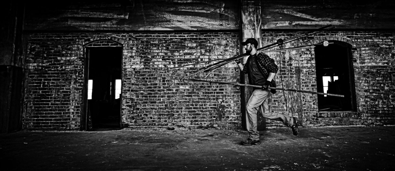 A man walking through an old building carrying pipes