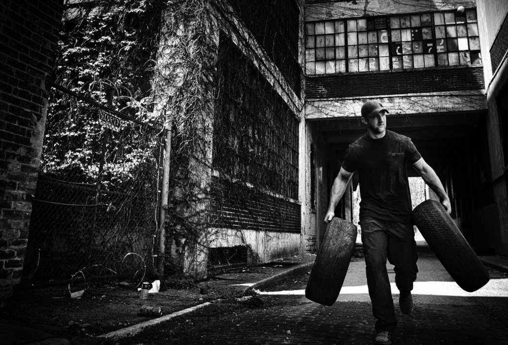 A man carrying two tires through and old facility
