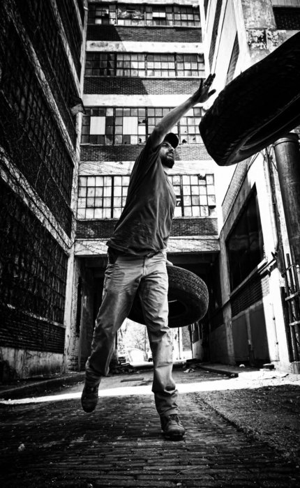 A working man tossing a tire