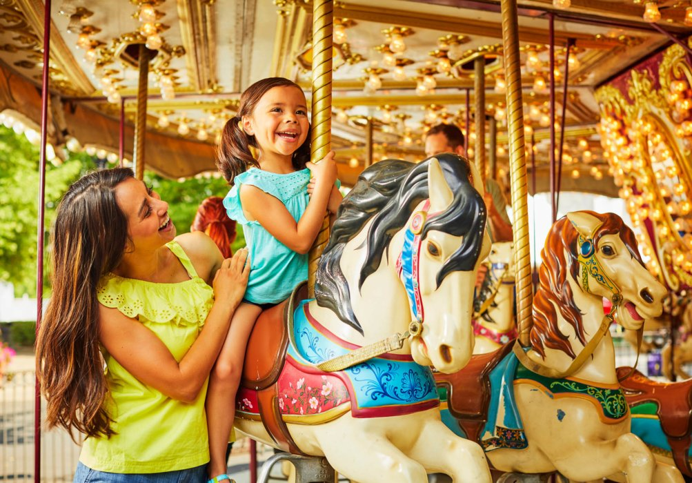 A mom and daughter on a merry go round - lifestyle photography