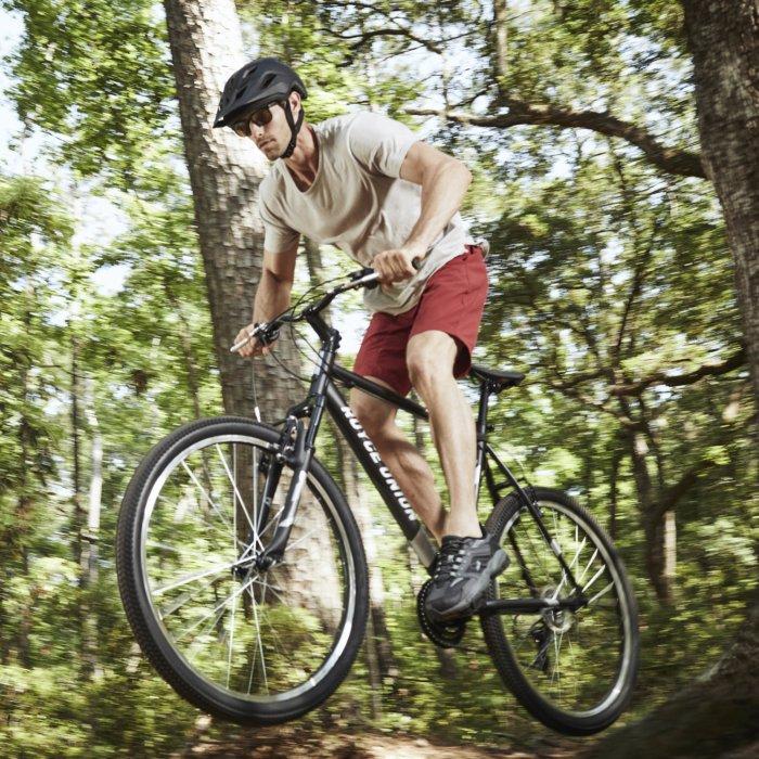A bike rider athlete making a jump in the wood on a bike