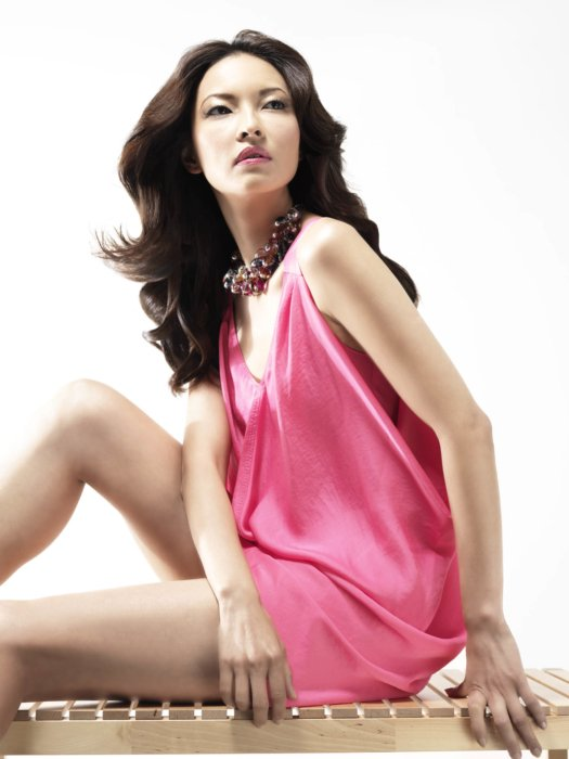 Beauty shot of a woman in a pink dress on a wooden bench