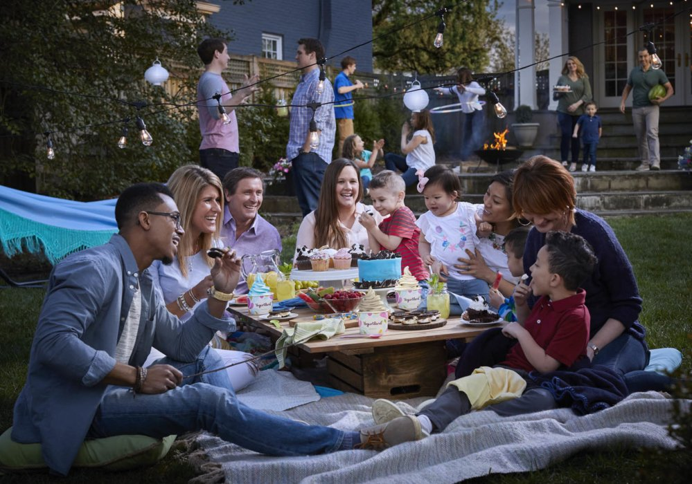 A outdoor dinner party having fun at dessert from sideview - lifestyle photography