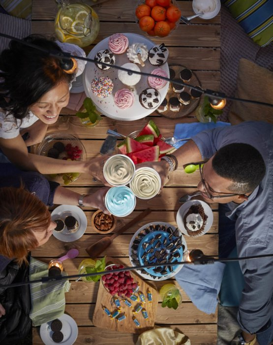 A outdoor dinner party having fun at dessert - food lifestyle photography