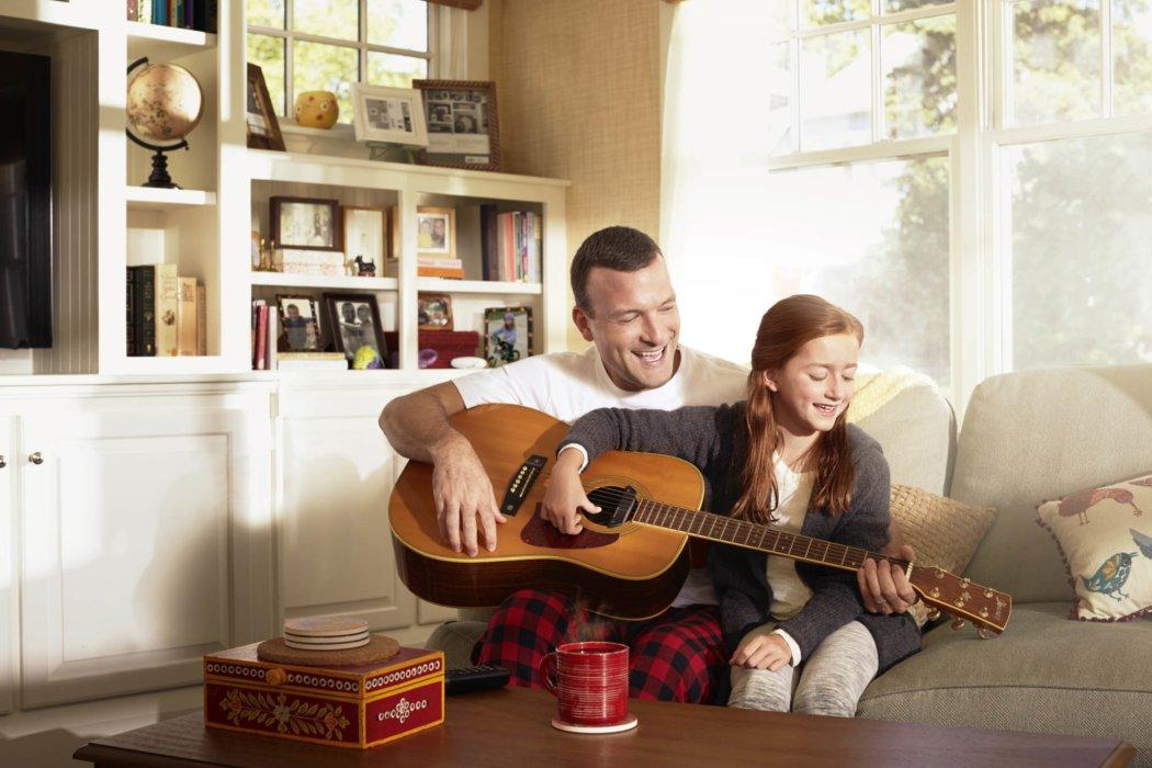 A dad teaching his daughter guitar