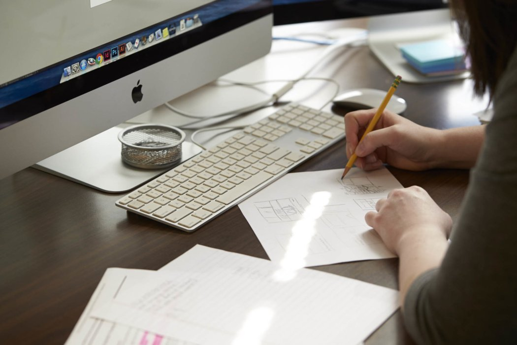 A woman at work with pencil and mac
