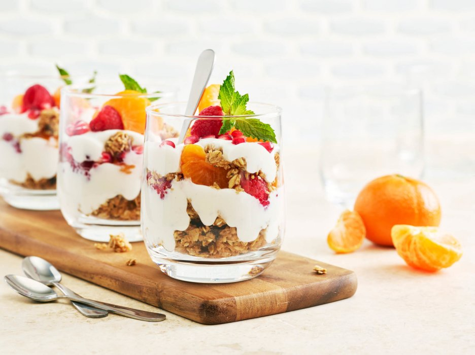 Yogurt parfait on wooden plate with oranges and fruits