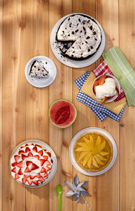 Desserts arranges on table with cakes, fruit, and yogurt