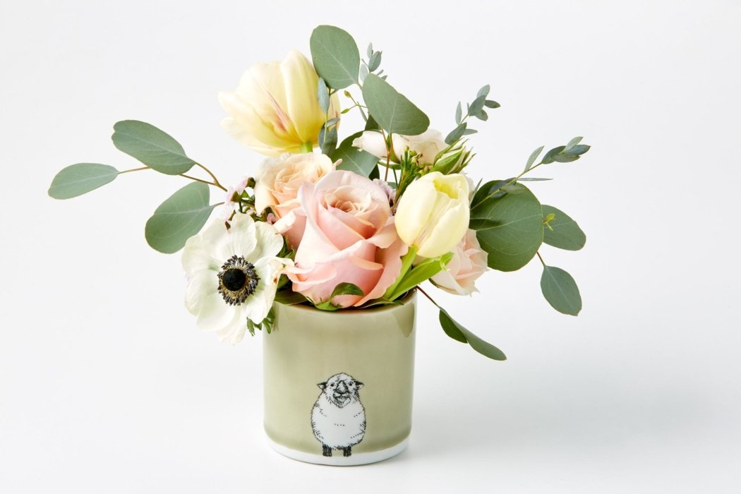 Flowers in a small cup with a sheep on it