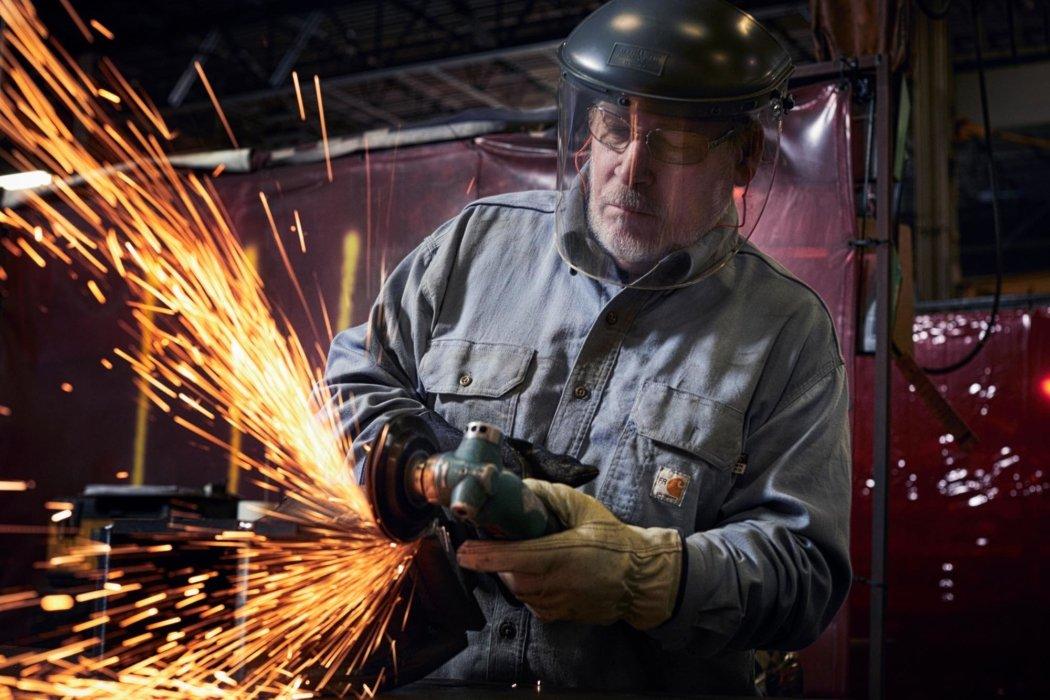Man with welding helmet sanding metal