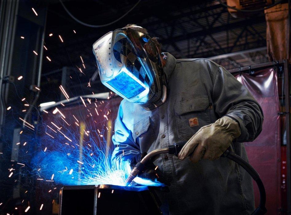 Man with welding helmet welding with a torch
