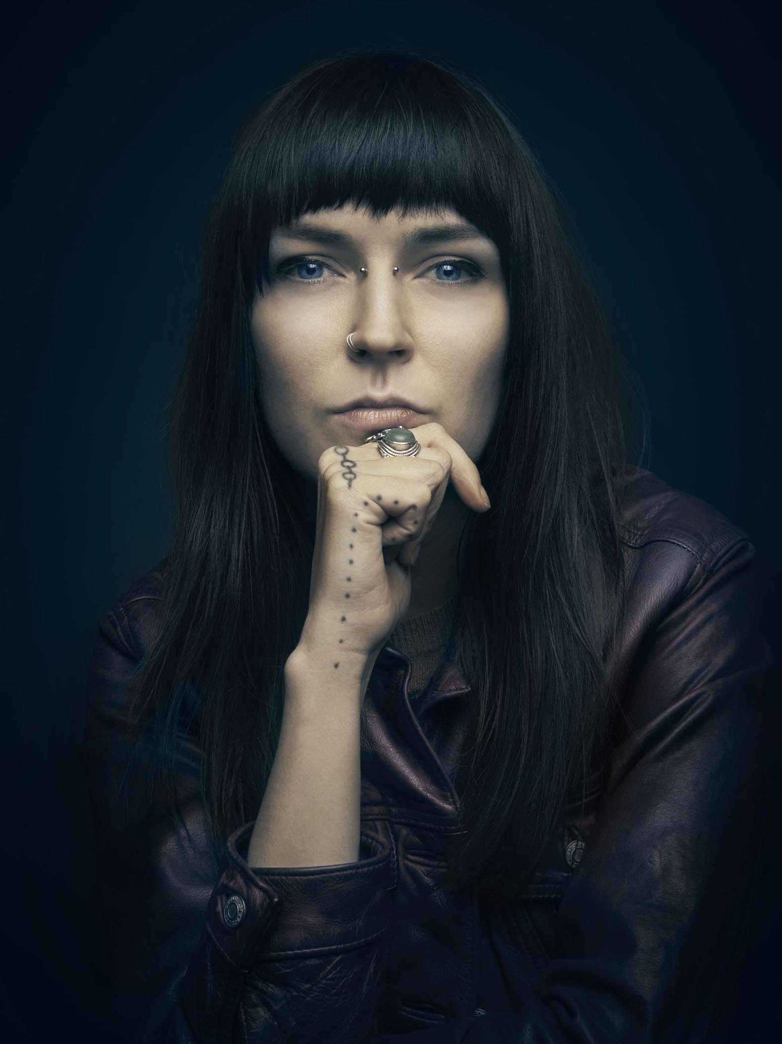 Portrait of a woman wearing leather with hand on chin