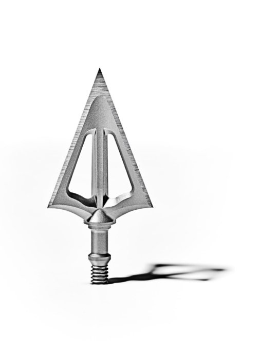 A close up of a steel arrow head on a white background