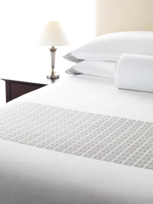 White textile fabric bedding in a made bed