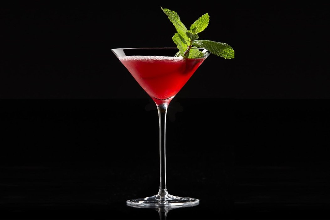 A red cocktail on a black background with a green garnish