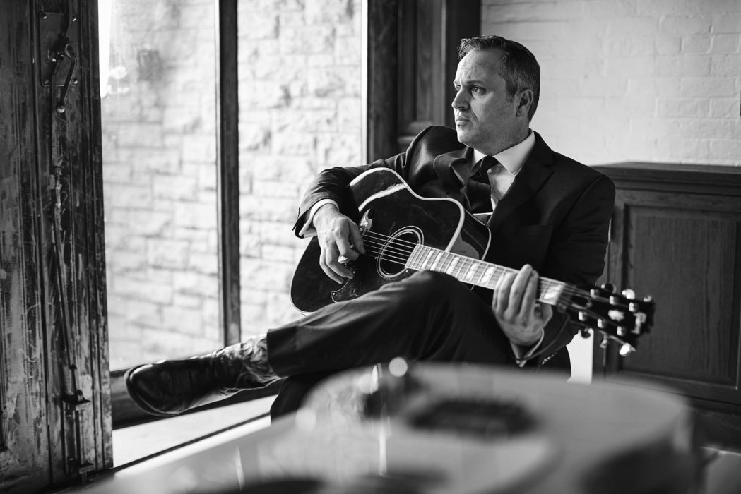 Portrait of a Musician with a guitar in a chair