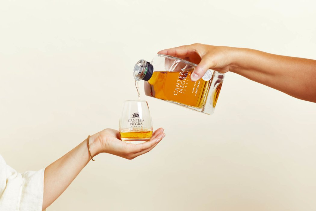 two women pouring tequila - pouring drink into hand holding glass - drink photography