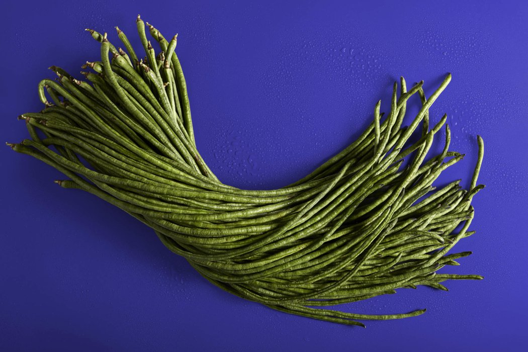 Food photography of string beans on a blue background