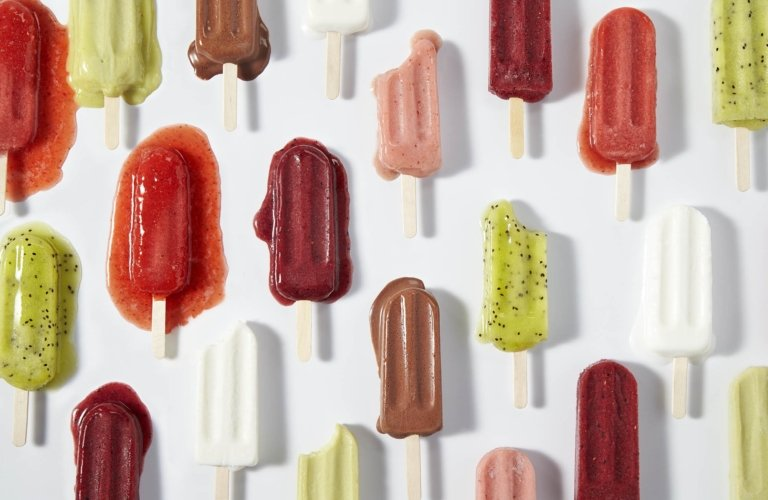 Food photography - real fruit popsicles melting on white background