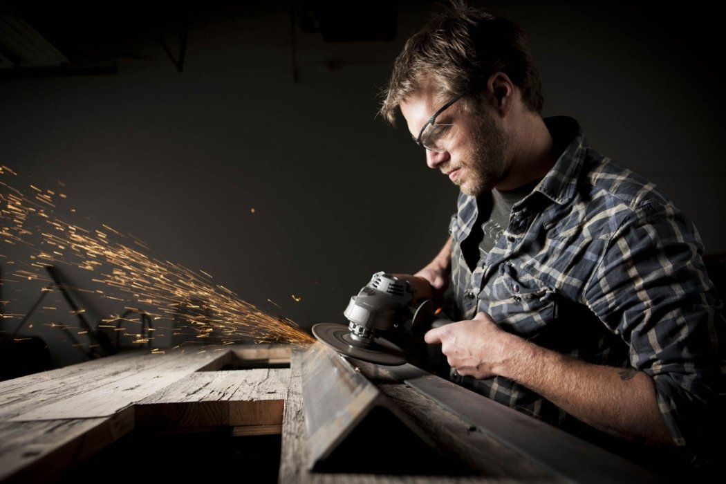 Portraits shot of a man working on steel with a sander