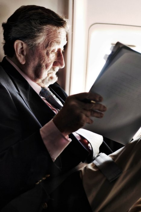 A portrait of a businessman reading paper on a plane