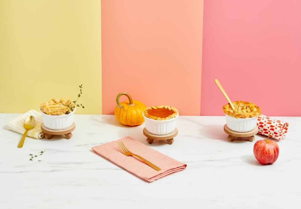 Three small pies in ramekins on a colorful background