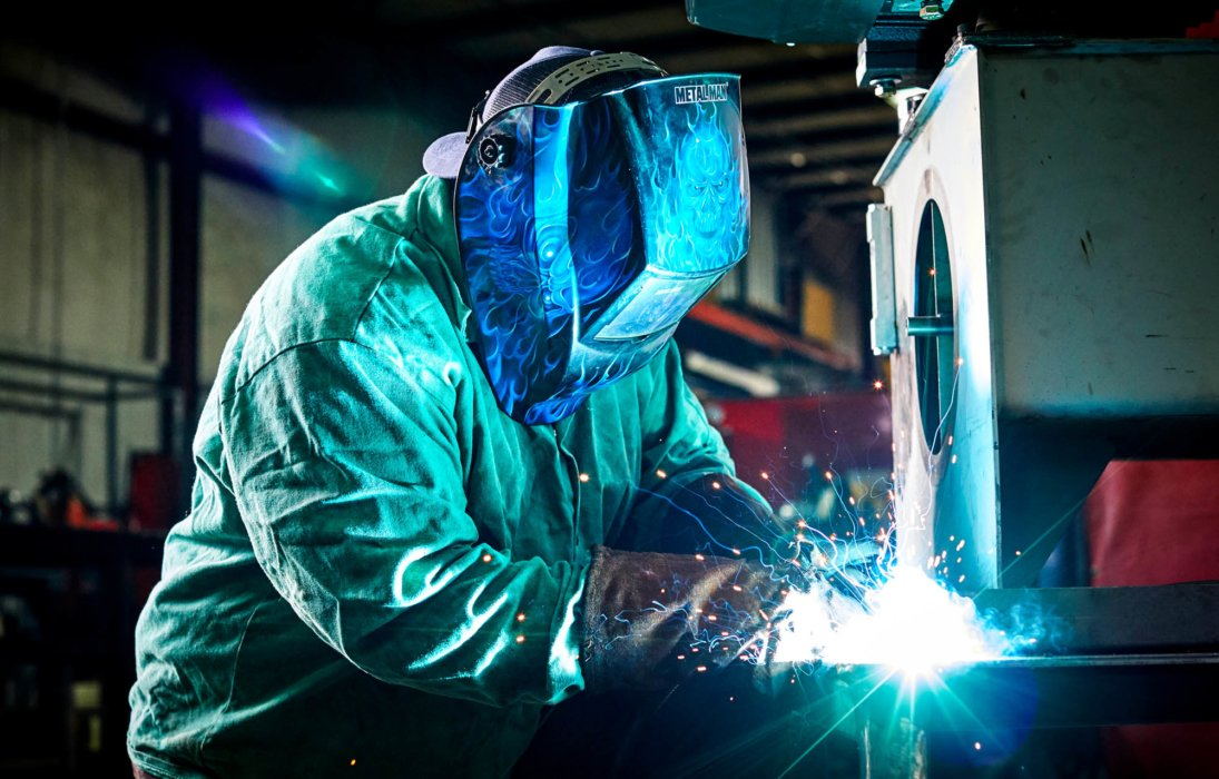 A man welding metal together in an industrial setting - industrial photography