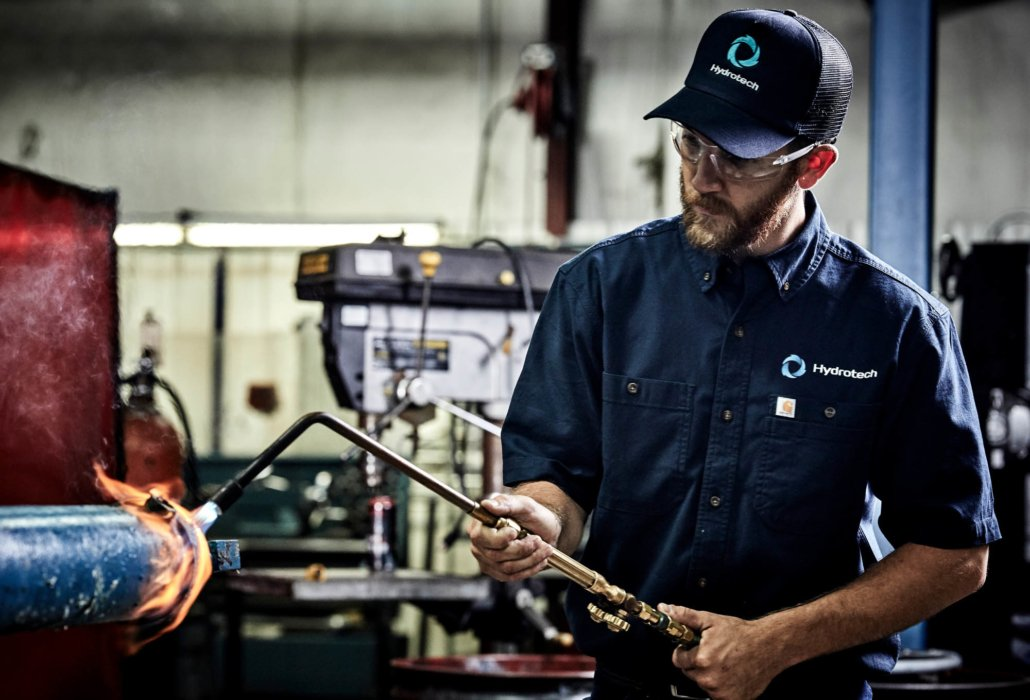 A man using a blow torch in an industrial setting - industrial photography