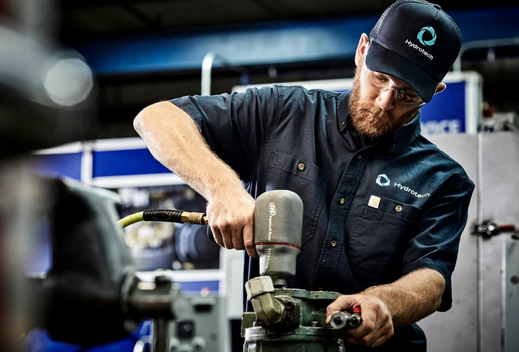 A man using an industrial drill in an industrial setting - industrial photography