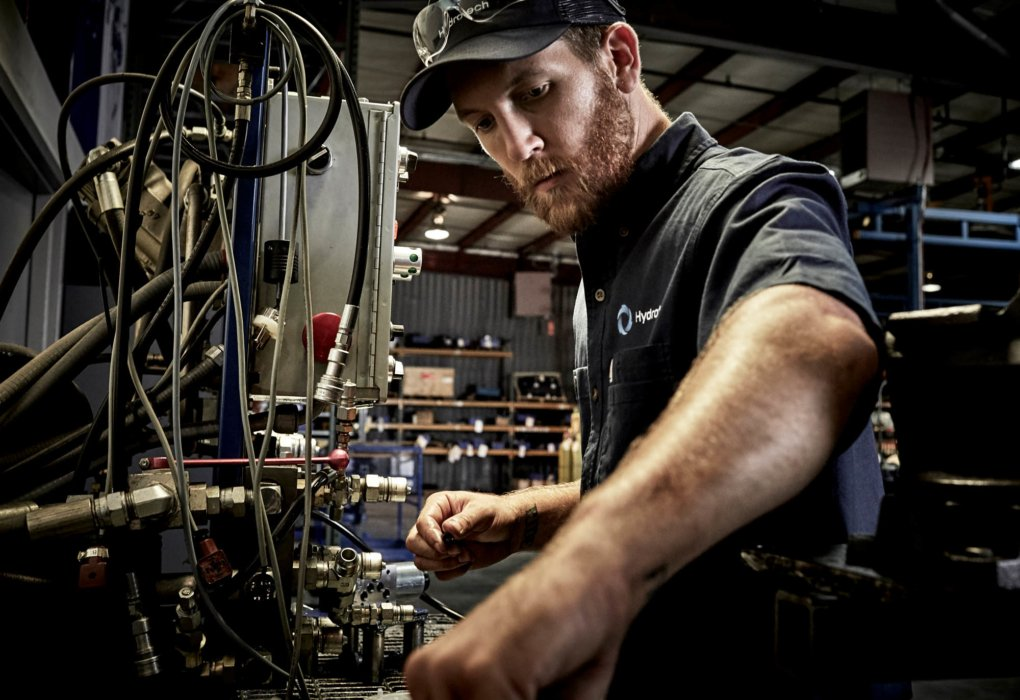 A man working on wires and cables with industrial equipment - industrial photography