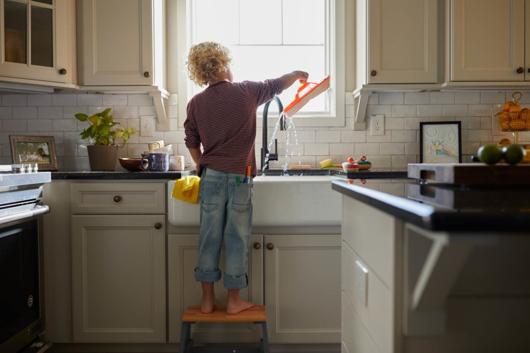 A boy playing with toys at sink in a modern designed kictchen - lifestyle photography
