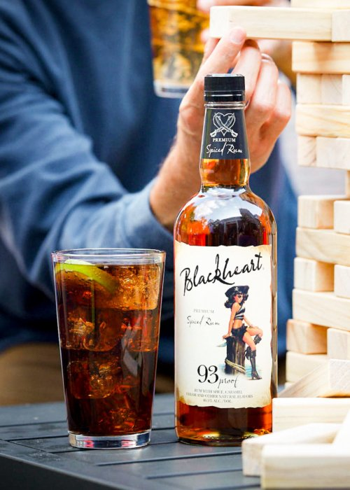 A bottle of blackheart rum with cola in a glass people playing Jenga - lifestyle drink photography