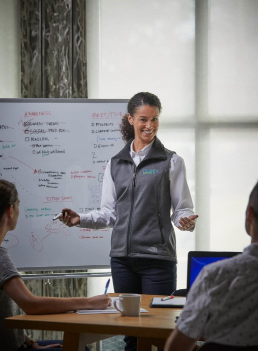 A woman at leading a group meeting with a white board - - corporate photography