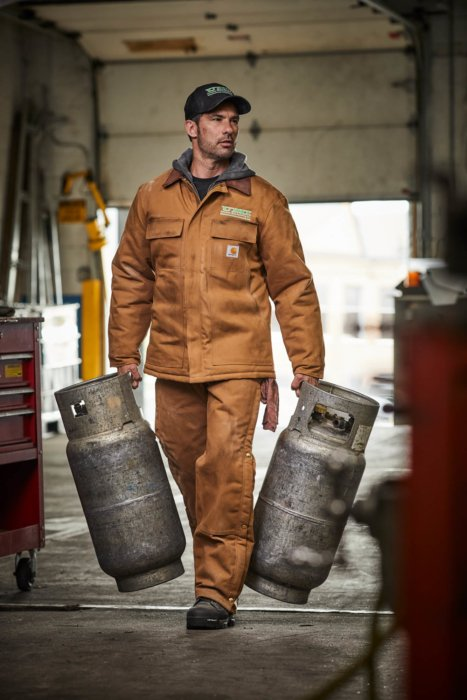 A man carrying two propane tanks in an industrial setting - work apparel photography