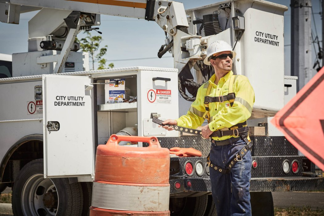 Man with helmet outside next to truck work apparel photography