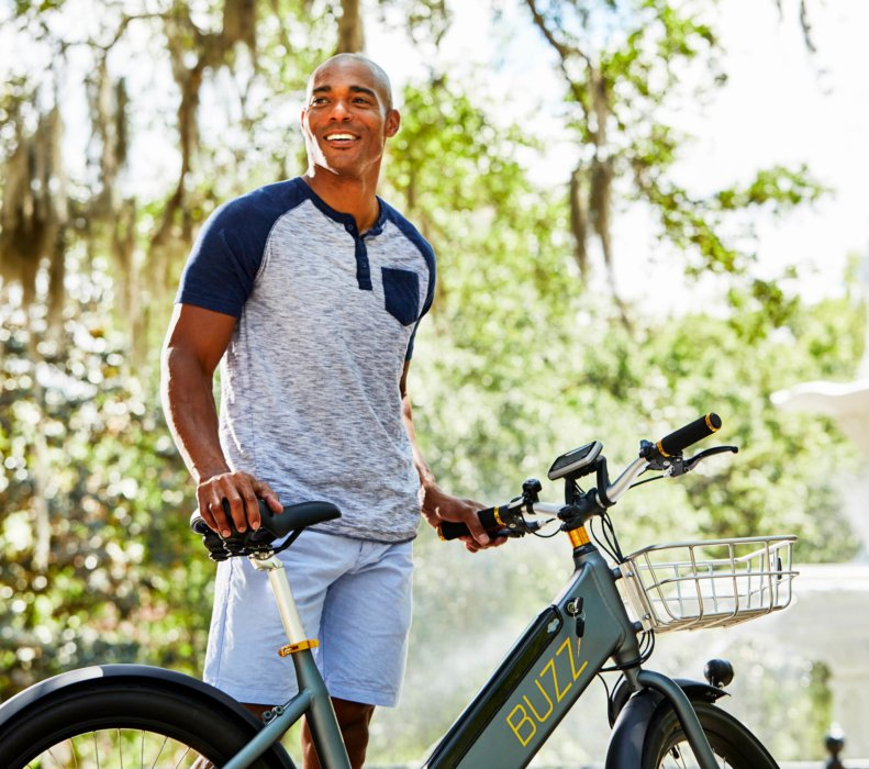 A young man riding a electric bike in a city park - product lifestyle photography