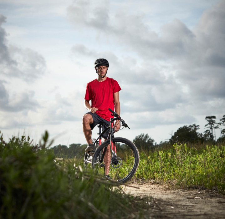 A young man standing with a bike on a dirt trail - Royce Union - product lifestyle photography