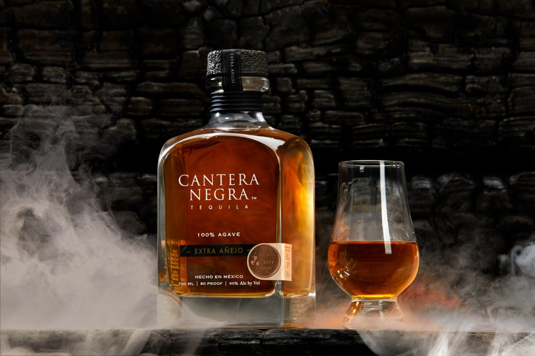 tequila bottle and glass surrounded by smoke after photo retouching