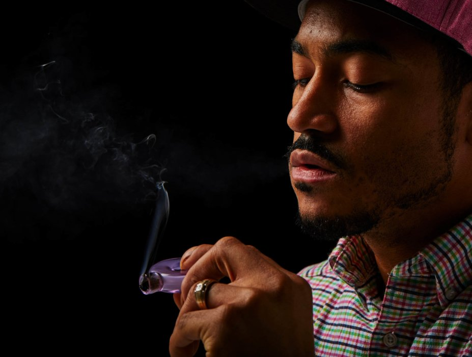 Man looking at purple pipe cannabis photography