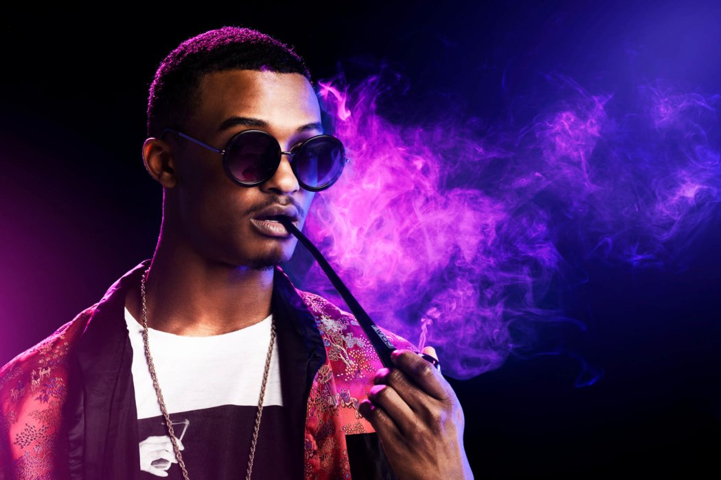 Purple light of man with rounded glasses smoking a pipe cannabis photography